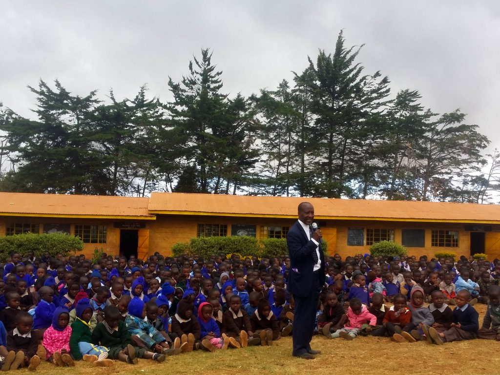 Mr. Franco Mbae the headteacher of Gundua Primary School addressing pupils and teachers during the closing day ceremony at the school