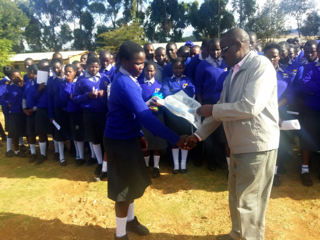 Stanley Kathurima deputy Principal of Gundua Secondary School gives an award to one of the best students during the closing ceremony