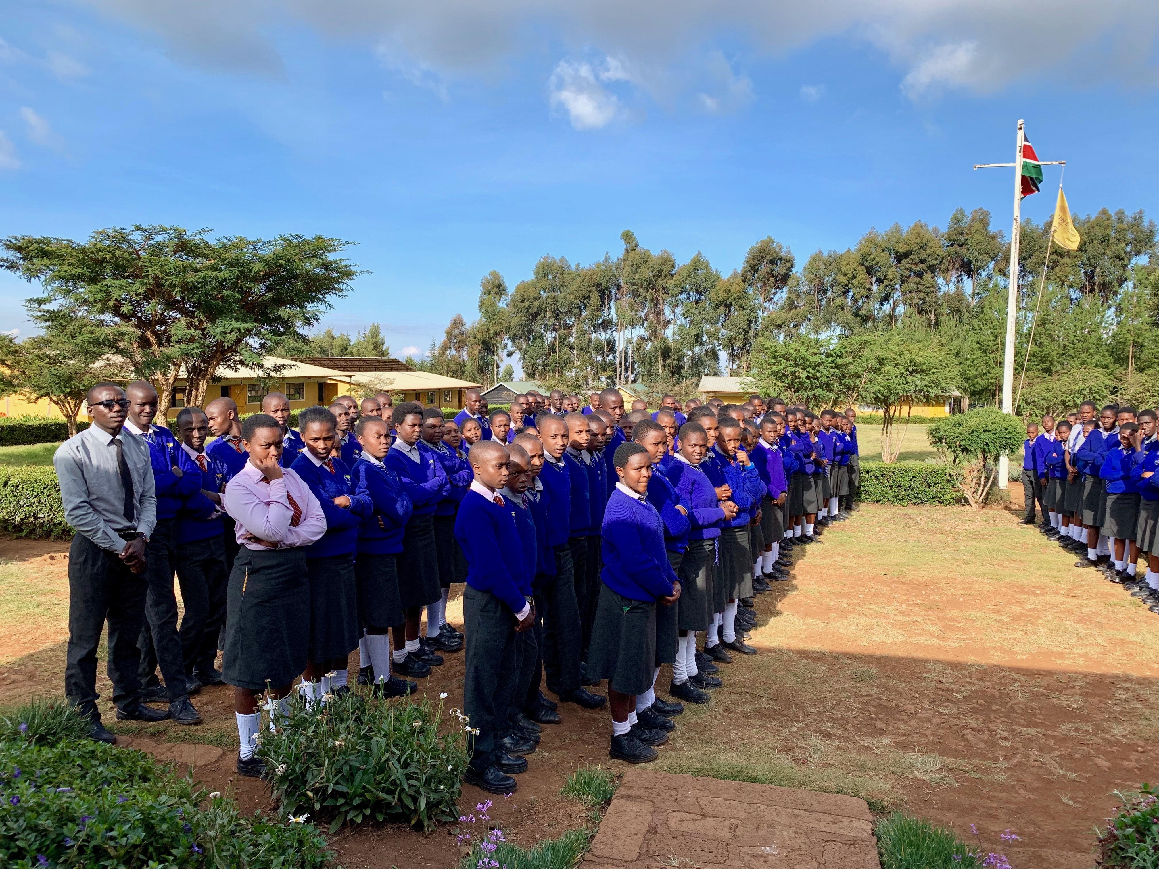 Studenter på Gundua Secondary hälsar besökarna med sång