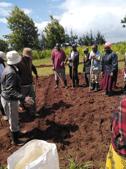 Maritati self help group members listening to the instruction from the agriculture extension officer on how to prepare the land before planting potatoes